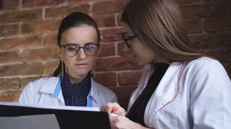 karşılaştırmak : Doctor female the girl explains to an Intern error in diagnosis and adjusts treatment assignment. Stok Video