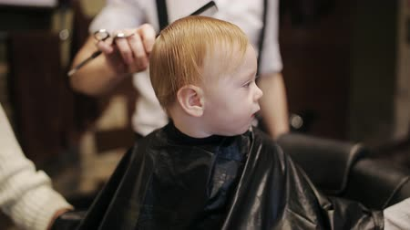 being prepared : A small child is being prepared for a haircut in a hairdresser