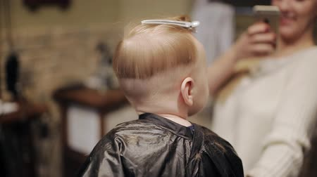 grzebień : Baby first hair cut time in a hairdressing salon Wideo