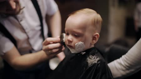 shaving foam : In a brutal men beauty salon a young child is shaved
