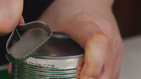 enlatamento : Close up of a hand using a manual can opener to open a can of food and removing the top of the lid.