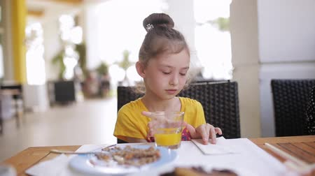 çiğnemek : Adorable girl having breakfast at outdoor cafe. Adorable girl drinking fresh juice
