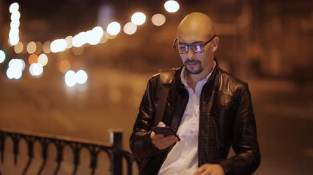 sending : Man sms texting using app on smart phone at night in city. Handsome young business man using smartphone smiling happy wearing suit jacket outdoors. Urban male professional in his 20s.