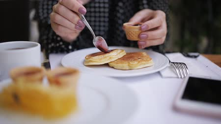 креп : Woman putting jam pancakes at the table in cafe