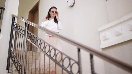 tárcsáz : A beautiful woman walks down the stairs with a tablet in hands