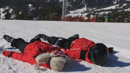 skier : Cheerful Couple Of Skiers Laying Down In Snow. Young Guys Have A Lot Of Fun Spending Winter Vacation In The Mountains.