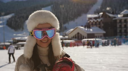вязание : Happy woman in a knitted sweater at the ski resort poses for the camera in the last light of the sun. Стоковые видеозаписи