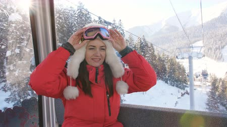 chairlift : The ski resort. The girl rides in the ski lift cabin and enjoy the beautiful snow-covered landscapes.