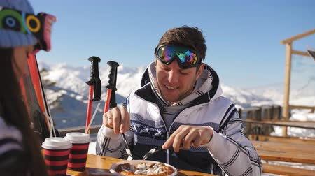 vin brulè : Couple of skiers having lunch at the restaurant on top of the mountain.