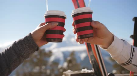 mulled wine : Couple of skiers drinking mulled wine on the mountain at lunch time. Close-up cups with mulled wine on the sky background.