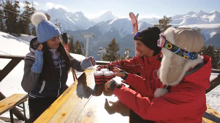 içecekler : Group of happy friends cheering with drink after skiing day in cafe at ski resort Stok Video