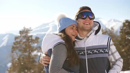 narciarstwo : Happy couple at the ski resort on a background of winter mountains hugging and flirting.