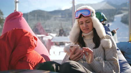 столовая гора : Young woman relaxing at an alpine ski resort. A girl uses a smart phone sitting in a cafe at a ski resort. Стоковые видеозаписи