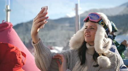 столовая гора : An attractive girl in a sweater and cap sitting in a outdoor cafe in the ski resort and taking a selfie on a smartphone. Стоковые видеозаписи