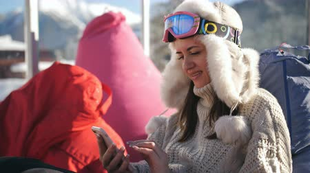 столовая гора : A girl uses a smart phone sitting in a cafe at a ski resort. Young woman relaxing at an alpine ski resort.