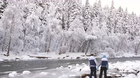 raquettes à neige : Happy couple standing on the mountain winter river and look into the distance. Winter landscape.