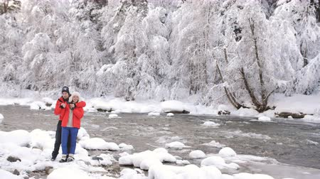 hayran olmak : Couple in love on the banks of winter river have fun and admire the winter nature. Stok Video