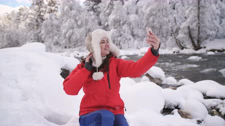 brotos : Beautiful girl in the mountains near winter river makes selfie on smartphone and smiling.
