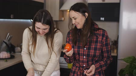 hayran olmak : Two girls in the kitchen talking and smell the tomatoes before preparing the salad.