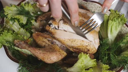 roston sült : Close-up woman cuts with a knife oven baked chicken. Family dinner.