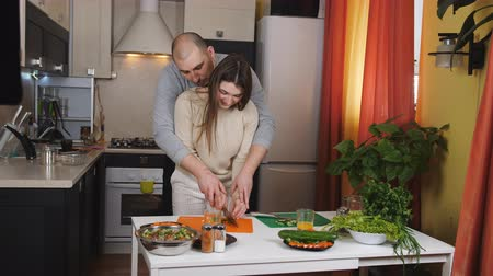 восхитительный : The husband embraces his wife in the kitchen and helping her chop the vegetables for the salad. Стоковые видеозаписи