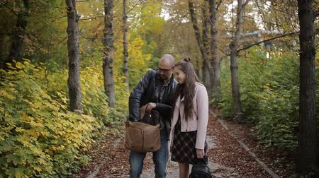 伝える : Father walking with daughter girl in the autumn Park and photograph it on camera 動画素材
