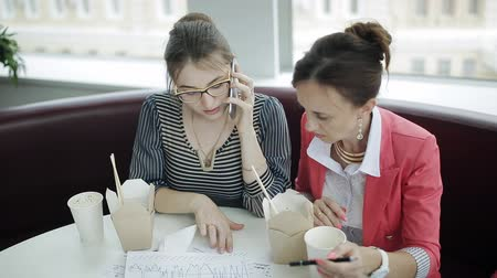 лапша : Two business women talking on the phone with the boss during lunch break Стоковые видеозаписи