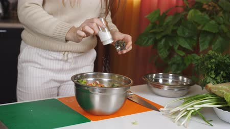 cebolinha : Woman adding salt in salad with vegetables in metal bowl.