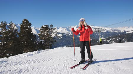 ascend : Female skier resting before the next descent from the mountain and admiring the winter scenery.