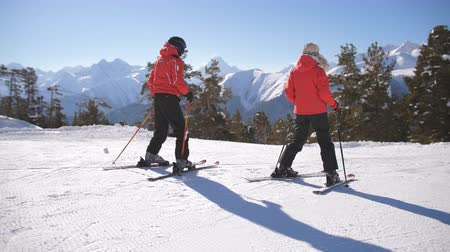 alineación : A family vacation at a ski resort. Couple of skiers on the mountain.