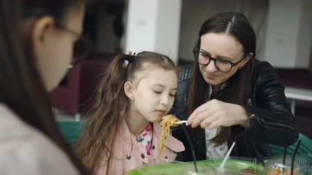 forced : Mom feeds younger daughter with a fork in a cafe. Family lunch in the cafe.