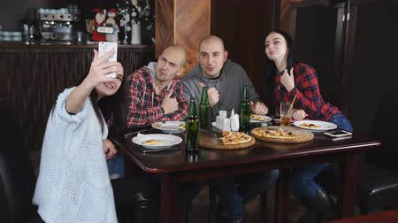 повод : The company of cheerful friends in the pizzeria. Girl doing a selfie with a smartphone in the pizzeria.