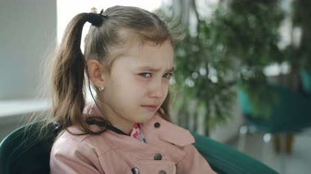 grimacing : Upset little girl crying in a cafe by the window.