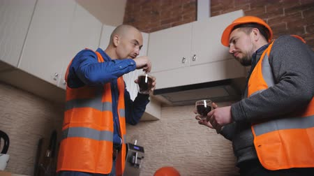 headwear : Two engineers in protective helmets and orange vests drinking coffee in the kitchen.