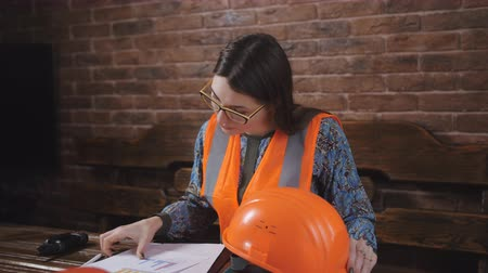 helmets : Portrait of a woman engineer in the workplace. Woman engineer in helmet and protective vest sits ha work Desk. Woman looking at camera and smiling.