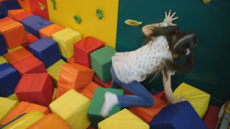 яма : Little girl plays in an entertainment trampoline center. child rolls cubes of foam rubber.