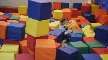 sport dzieci : Girl 7 years playing in the trampoline centre with soft colored cubes.