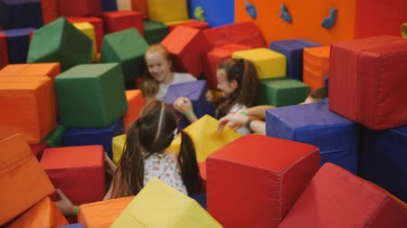 leaping : Childrens entertainment center. Battle cubes in a soft trampoline center. Teen girls fooling around and having fun with big soft cubes. Stock Footage