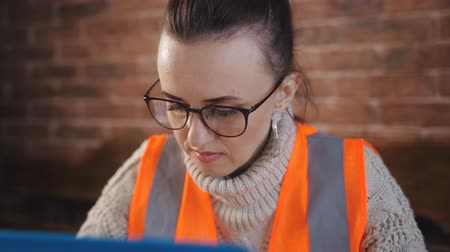 документация : Focused woman Builder works with laptop and with the technical documentation in the room at the construction site.