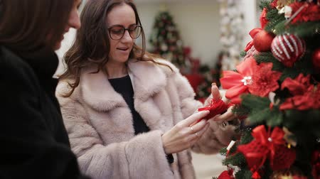 мишура : Two women shoppers choose the Mall Christmas toys to decorate the house on Christmas eve.