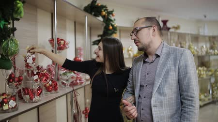 festoon : The loving couple selects the Christmas decorations in the supermarket. A woman considering Christmas balls and offers them to buy his husband.
