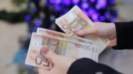 allowance : The woman believes Euro banknotes on a background of the Christmas tree. Time to buy holiday gifts.
