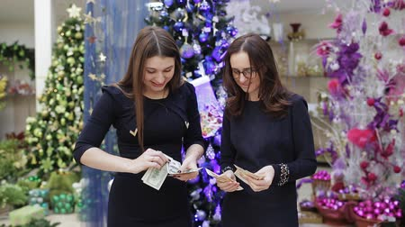 scelta migliore : Two women find revenue in a new year supermarket on the background of Christmas decorations.