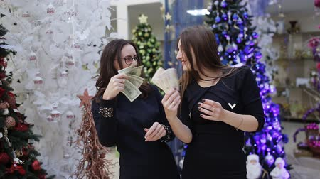 banknot : Two women with money in their hands dancing on the background of Christmas trees.