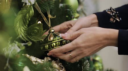 wybór : Close up shot of a woman shopping for christmas toys alone. Close-up of female hand picks a Christmas ball and examines it