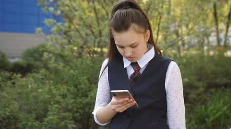 ninhada : Schoolgirl teen reads the message on the smartphone near the school building.