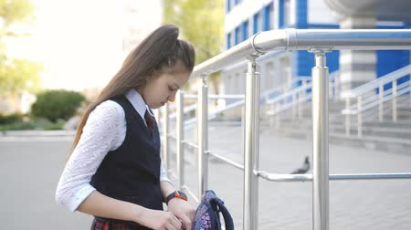 go to school : Sad high school girl returns home from school. Schoolgirl teenager throws the backpack on his shoulder and walks home after school.