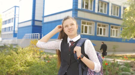 ninhada : Portrait of a schoolgirl teenager with a backpack near the school. Girl teenager straightens hair standing near the school.
