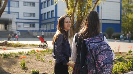 accompagnare : Mom takes a teenage daughter to school. Mother and daughter a teenager go to school together.