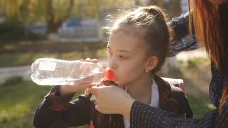after school : Little girl in school uniform drinks water from a plastic bottle. Mother adjusts her daughter tie, and the girl quenches thirst with water from a plastic bottle.